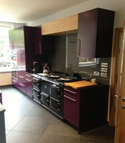 Purple cabinetry that complements the range cooker's smart black finish